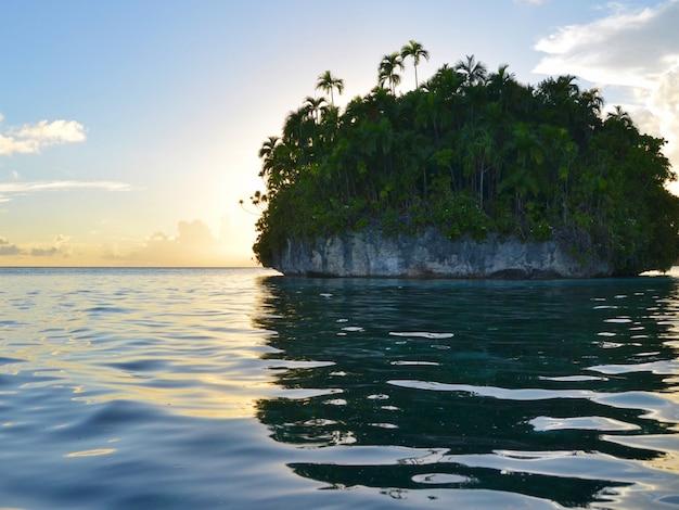 A vista cênico da ilha no oceano pacífico com o fundo do por do sol.