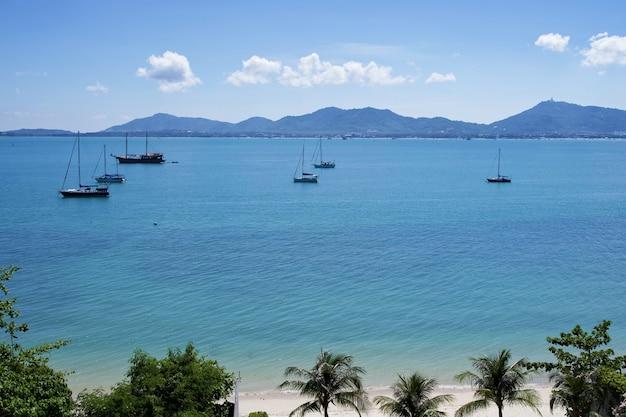 A vista cênico da praia e do oceano tropicais da areia branca em phuket, tailândia.