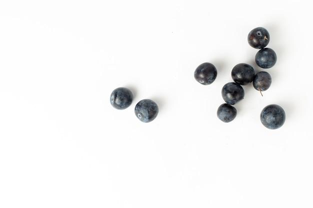 A vista de cima amora-preta fresca, frutas azedas e escuras no fundo branco