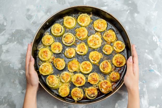 A vista de cima assou anéis de abóbora dentro de uma grande frigideira preta salgada e saborosa na mesa leve prato de comida de vegetais