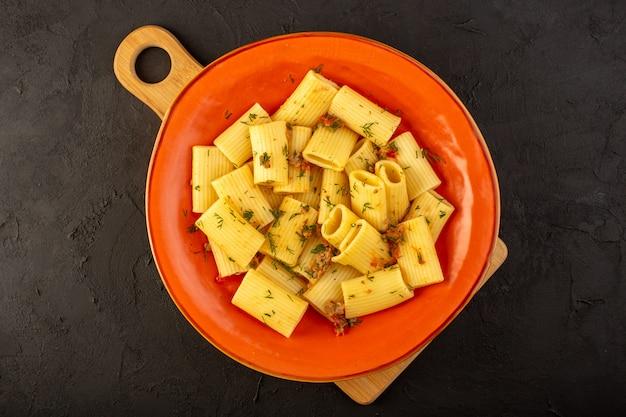 A vista de cima da massa italiana cozida saborosa e salgada dentro de um prato redondo de laranja na mesa escura