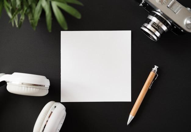 A vista de cima de uma caneta de papel em branco plana e de fones de ouvido e uma câmera de filme na superfície preta da mesa