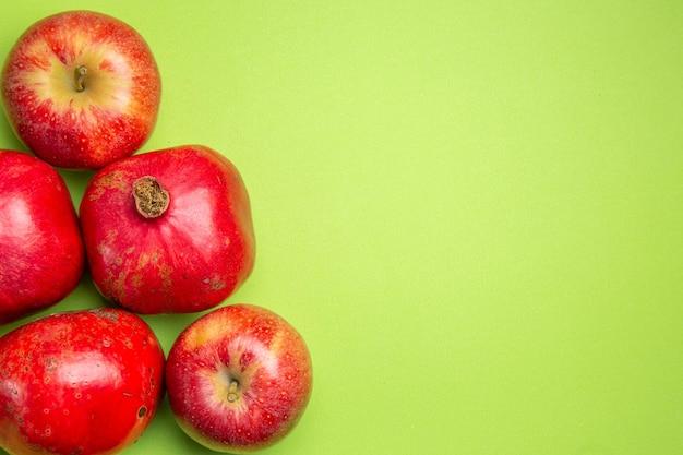 A vista de cima em close frutifica as apetitosas maçãs e romãs no fundo verde
