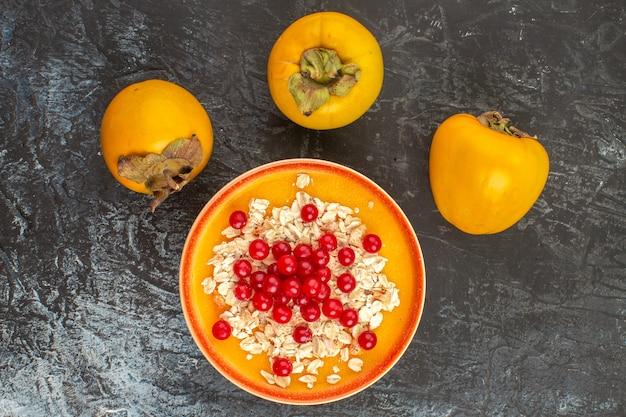 A vista de cima em close-up bagas persimmmm as frutas apetitosas na tigela