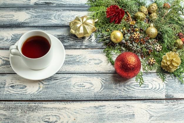 A vista de cima enfeita uma xícara de galhos de árvore de abeto de chá no espaço livre de fundo de madeira