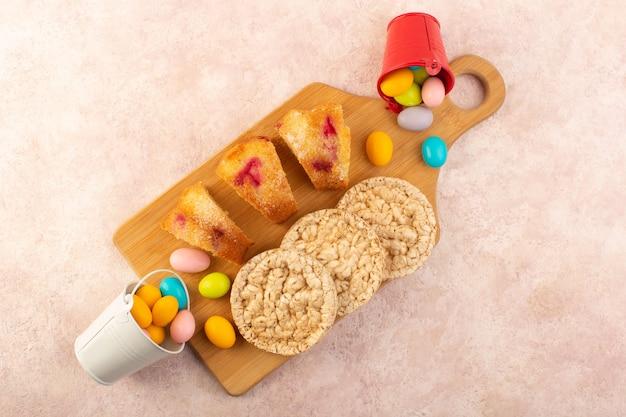 A vista de cima fatias de bolo de cereja com doces e biscoitos no bolo de mesa rosa brilhante biscoito açúcar