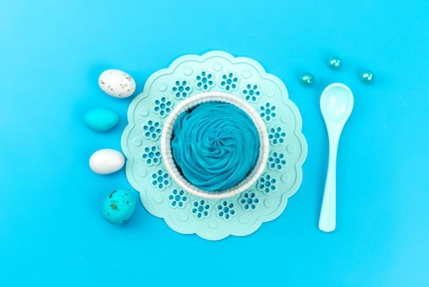 A vista de cima ovos e sobremesa azul e branco, com branco, colher isolada em azul, cor de comida