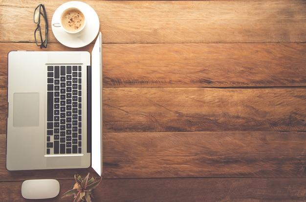 A vista de cima tem um laptop, café, copos na mesa e há espaço para o seu texto inp
