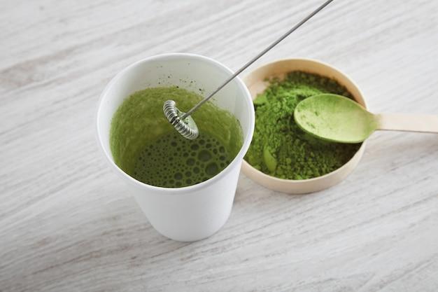 A vista de cima tira o copo de papel branco e o chá matcha orgânico premium do japão na mesa de madeira, pronto para a preparação de café com leite de maneira moderna