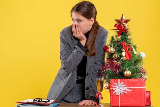 A vista de frente surpreendeu a garota em pé atrás da mesa olhando algo árvore de natal e coquetel de presentes