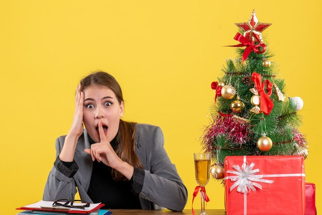 A vista de frente surpreendeu a garota sentada à mesa fazendo shh sinal perto da árvore de natal e coquetel de presentes