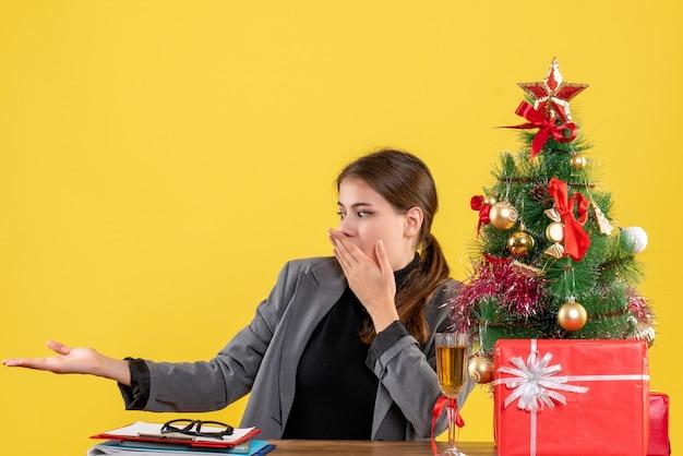 A vista de frente surpreendeu a garota sentada à mesa mostrando algo perto da árvore de natal e um coquetel de presentes