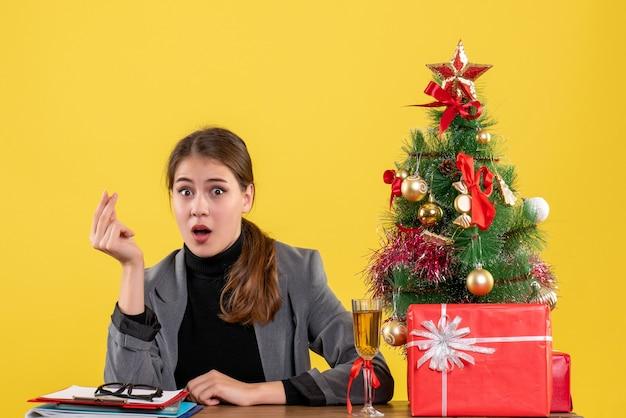 A vista de frente surpreendeu a garota sentada na mesa mostrando um gesto de dinheiro, árvore de natal e coquetel de presentes