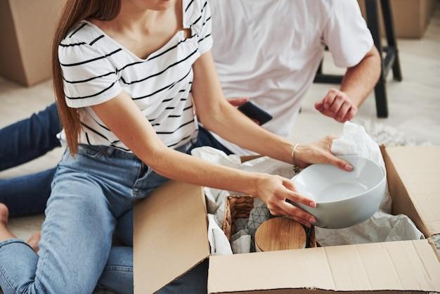 A vista de partículas do casal em seus novos apartamentos desempacota os pratos das caixas.