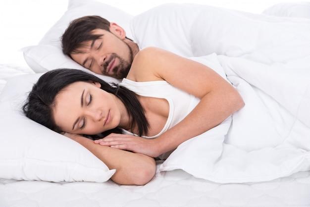 A vista de um par feliz novo está dormindo na cama.