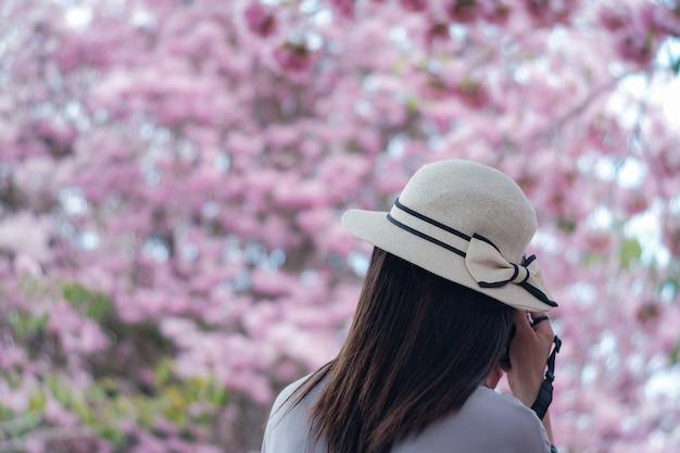 A vista de uma mulher de viagem com chapéu agradável está tomando retratos no fundo cor-de-rosa da flor.