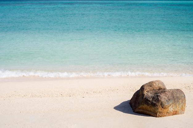 A vista de uma rocha na praia tropical na ilha tailandesa de lipe com areia branca, água do mar azul-turquesa e céu azul