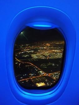 A vista do avião para as luzes da cidade à noite.
