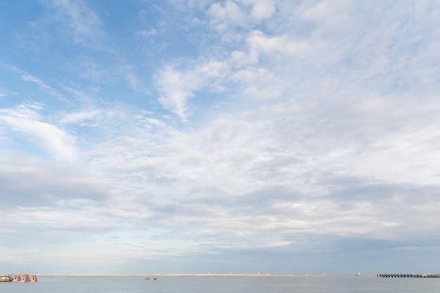 A vista do mar e do céu azul com uma pequena nuvem.