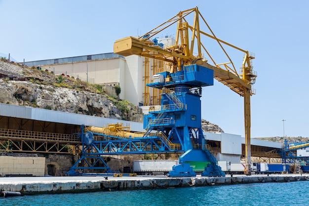 A vista do porto industrial com um grande guindaste azul trabalhando no cais da cidade de valletta.
