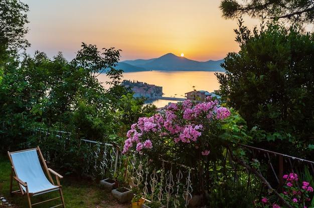 A vista do terraço ao pôr do sol sobre a ilhota do mar sveti stefan (montenegro, perto de budva)