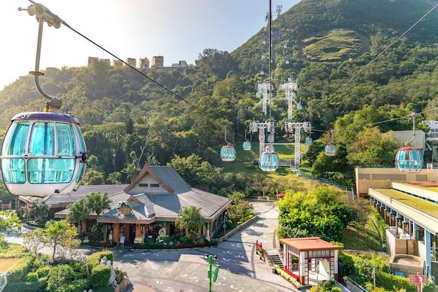 A vista ensolarada do teleférico e do parque temático perto do oceano
