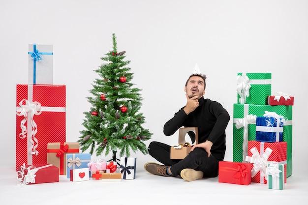 A vista frontal de um jovem sentado ao redor do feriado apresenta-se na parede branca