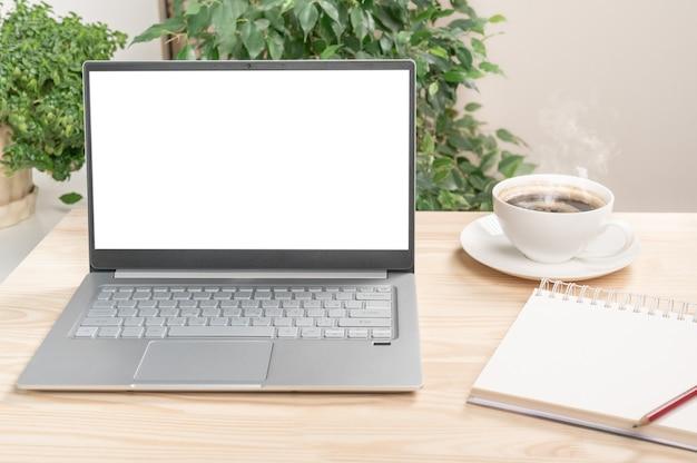 A vista frontal do laptop está na mesa de trabalho com o notebook e a xícara de café. laptop ou notebook com tela em branco na mesa de madeira em casa ou em um escritório moderno