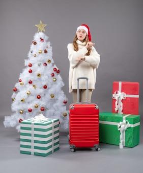 A vista frontal surpreendeu a garota com uma mala vermelha em pé perto da árvore de natal