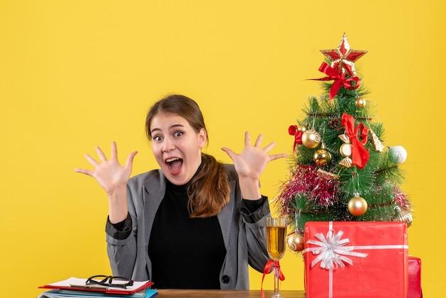 A vista frontal surpreendeu a garota feliz sentada na mesa com as mãos abertas, árvore de natal e coquetel de presentes