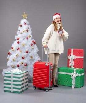 A vista frontal surpreendeu a garota loira com chapéu de papai noel segurando um despertador vermelho perto da árvore de natal branca e presentes