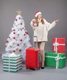 A vista frontal surpreendeu a menina loira com chapéu de papai noel segurando um despertador vermelho perto da árvore de natal branca e caixas de presente