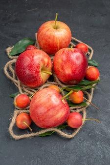 A vista lateral de close-up frutifica as apetitosas maçãs cerejas com folhas de corda