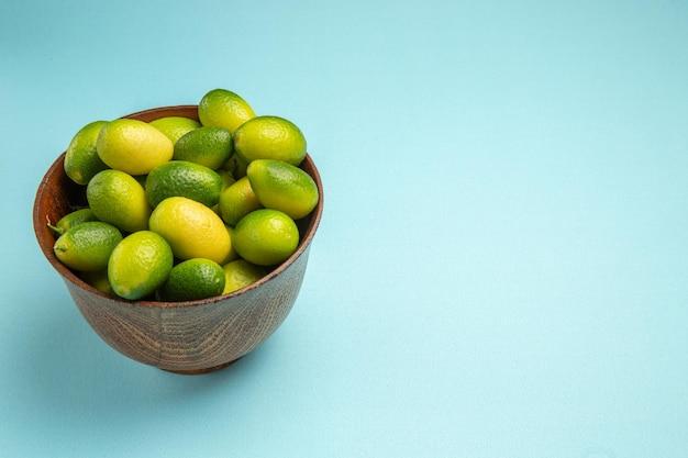 A vista lateral de close-up frutifica as frutas verdes apetitosas no fundo azul