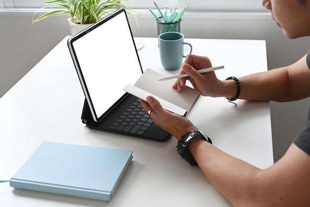 A vista lateral de um designer gráfico está tomando nota enquanto trabalha com um tablet em seu espaço de trabalho criativo.