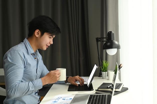 A vista lateral de um designer gráfico está trabalhando com o tablet do computador e tomando café em seu espaço de trabalho pela manhã.
