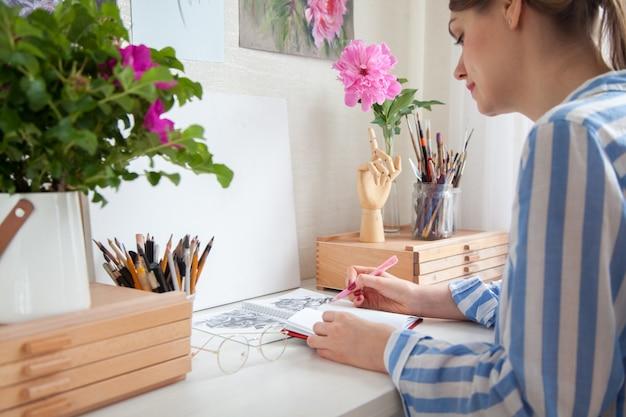 A vista lateral de uma jovem artista caucasiana preenche um planejador diário, escreve uma lista de tarefas em um caderno sentado em uma mesa de trabalho com gavetas com materiais para criatividade. conceito de criatividade e hobby