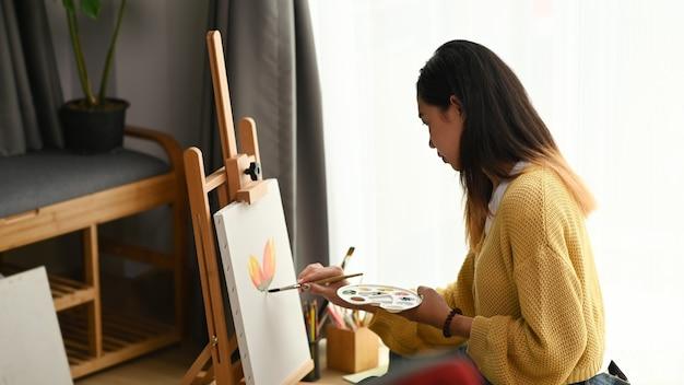 A vista lateral de uma pintora está fazendo um desenho com tinta de pôster em seu espaço de trabalho.