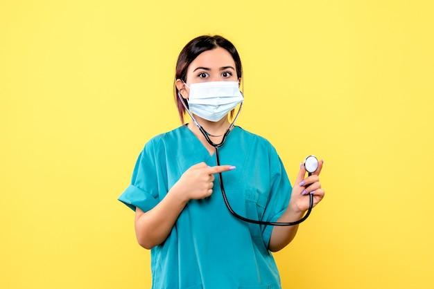 A vista lateral do médico na máscara aponta para o estetoscópio