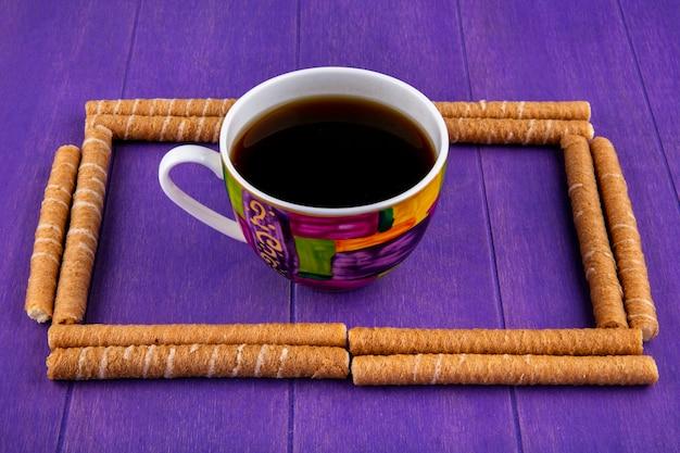 A vista lateral do teste padrão das varas crocantes ajustou-se na forma quadrada com a xícara de café no centro no fundo roxo