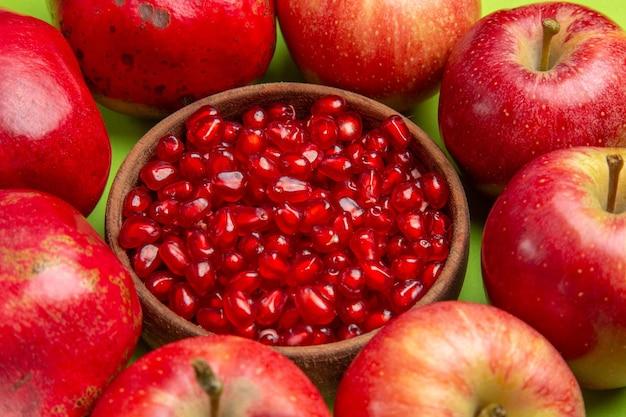 A vista lateral frutifica as sementes apetitosas de romã na tigela marrom três maçãs sobre a mesa