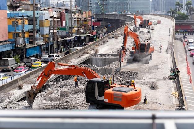 A vista na estrada da construção da estrada trabalha com máquina escavadora vermelha.