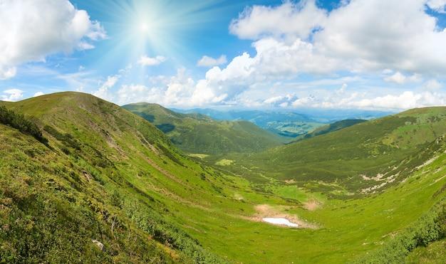 A vista panorâmica do prado da montanha do verão com a floresta de zimbro e a neve permanece no cume à distância. três tiros costuram a imagem.