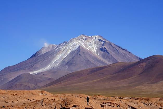 A vista panorâmica do viajante em pé de frente para a montanha multicolor.