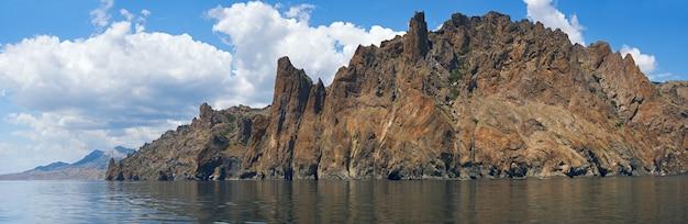 A vista sobre a rocha karadag (reserva no lugar do antigo vulcão extinto) do lado de um navio de excursão (crimeia, ucrânia). imagem do ponto de sete tiros.