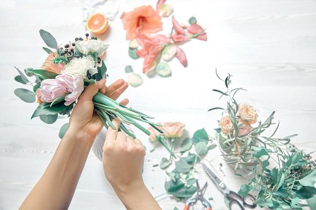 A vista superior cortou a imagem do florista fêmea que arranja um ramalhete com flores usa ferramentas no fundo branco do woodem. entrega de flores. copie o espaço. local de trabalho e conceito profissional