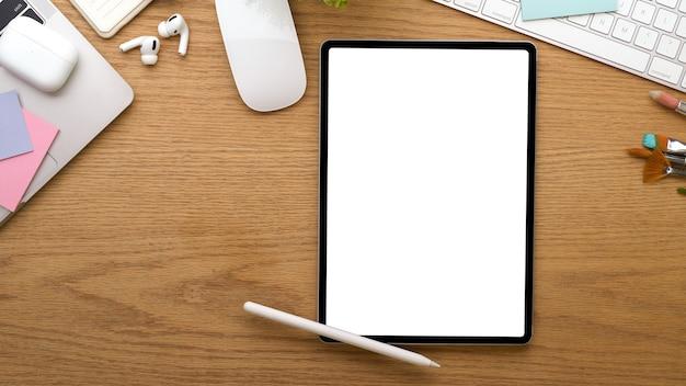 A vista superior da área de trabalho com tablet digital inclui acessórios de traçado de recorte e artigos de papelaria na mesa de madeira