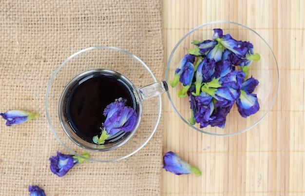 A vista superior da ervilha floresce a bebida saudável na tabela de madeira da prancha.