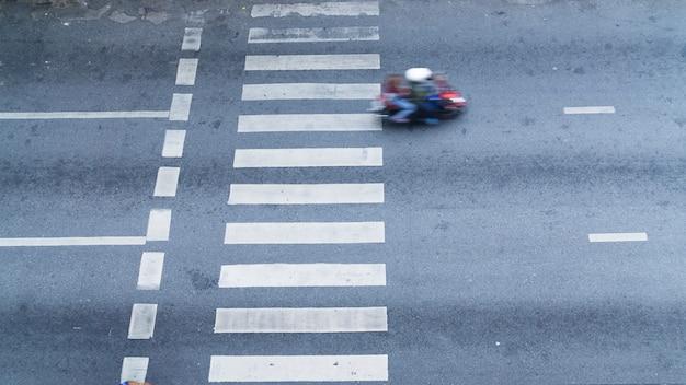 A vista superior da faixa de pedestres com o transporte na estrada.