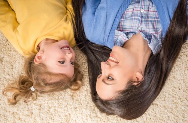 A vista superior da mãe feliz e da criança bonito está encontrando-se no assoalho.